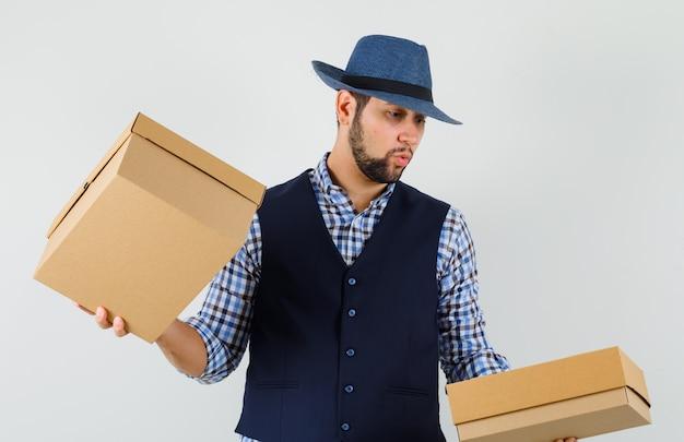셔츠, 조끼, 모자에 골 판지 상자를 들고 호기심, 전면보기를 찾고 젊은 남자.