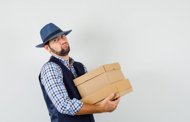 シャツ、ベスト、帽子で段ボール箱を保持し、暗い顔をしている若い男。正面図。