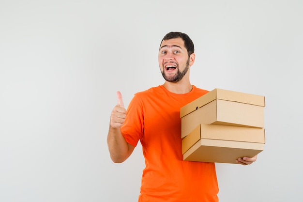 Young man holding cardboard boxes with thumb up in orange t-shirt and looking optimistic , front view.