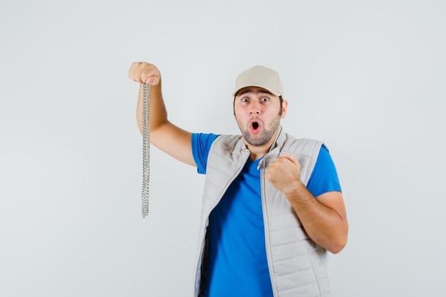 Giovane che tiene collana a catena in t-shirt, giacca, berretto e sembra agitato. vista frontale.