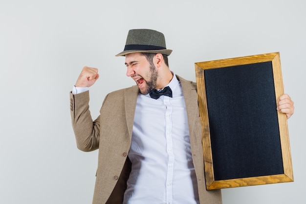 Young man holding chalkboard with winner gesture in suit, hat and looking blissful , front view.