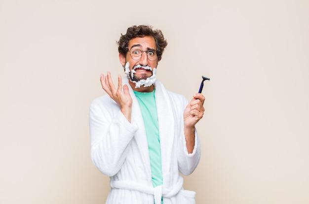 頬を抱えて痛みを伴う歯痛に苦しんでいる若い男、気分が悪く、惨めで不幸で、歯科医を探しています