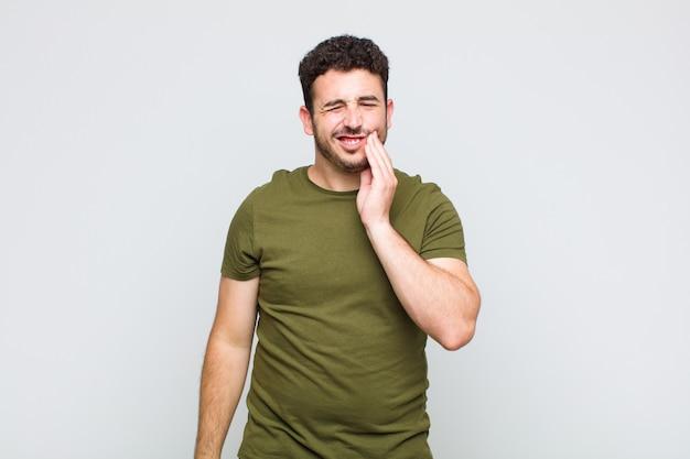 Молодой человек держится за щеку и страдает от болезненной зубной боли, чувствует себя плохо, несчастно и несчастно, ищет стоматолога
