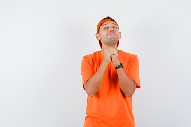 オレンジ色のtシャツとキャップでジェスチャーを祈って握りしめられた手を握り、楽観的に見える若い男