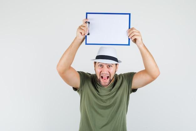 緑のtシャツと帽子で頭の上にクリップボードを保持し、狂ったように見える若い男