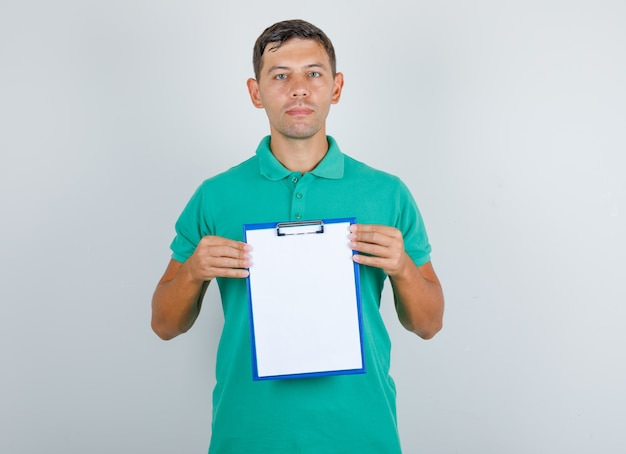Молодой человек, держащий буфер обмена и смотрящий на камеру в зеленой футболке, вид спереди.