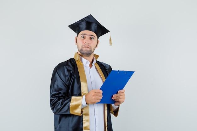 클립 보드를 들고 대학원 유니폼에 입술을 물고 의아해 찾고 젊은 남자. 전면보기.