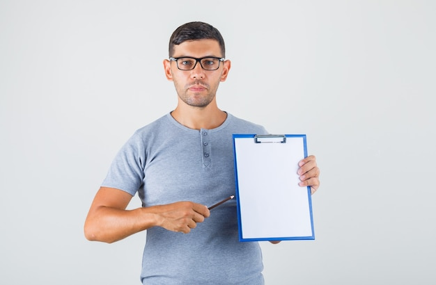 Young man holding clipboard and pencil in grey t-shirt, glasses