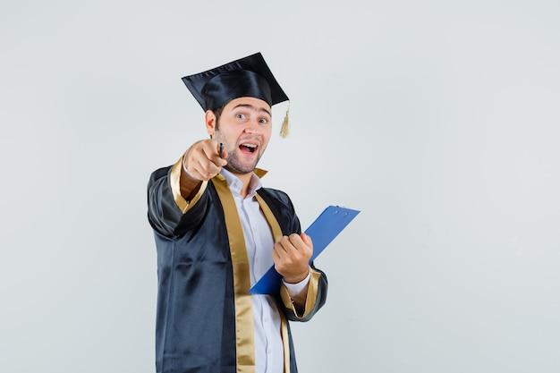 クリップボードを持って、卒業式の制服を着たカメラを指して、楽観的な正面図を見て若い男。