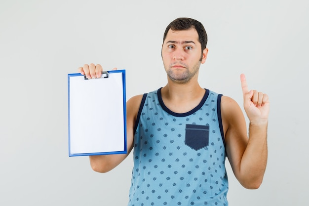Young man holding clipboard, pointing up in blue singlet and looking puzzled.