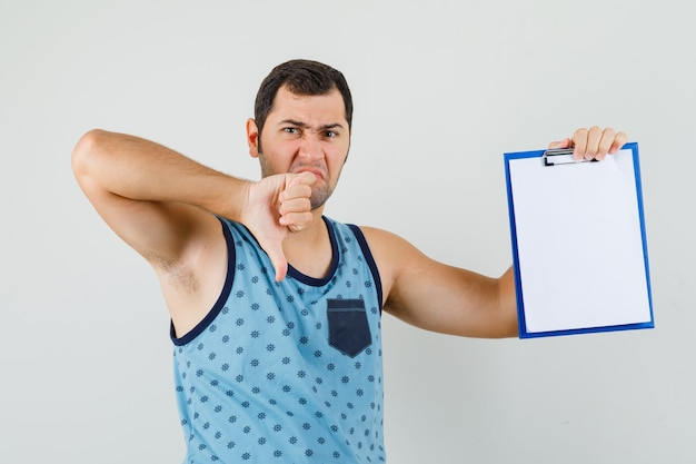 Young man holding clipboard, showing thumb down in blue singlet and looking discontent.