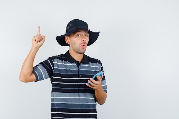 티셔츠, 모자 전면 보기를 가리키는 동안 클립보드를 들고 있는 젊은 남자.