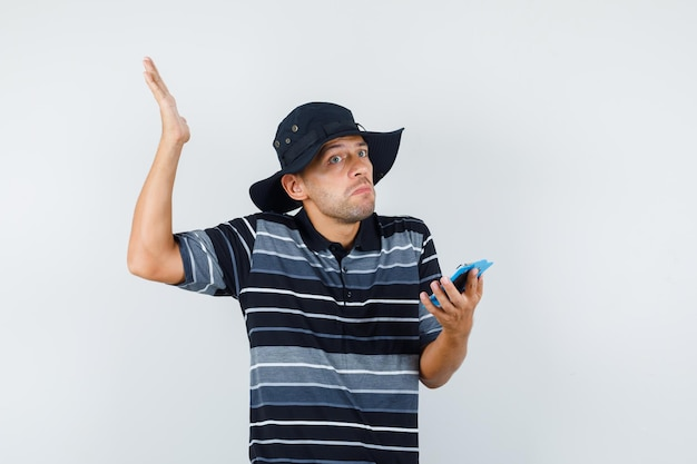 Young man holding clipboard with helpless gesture in t-shirt, hat and looking confused , front view.