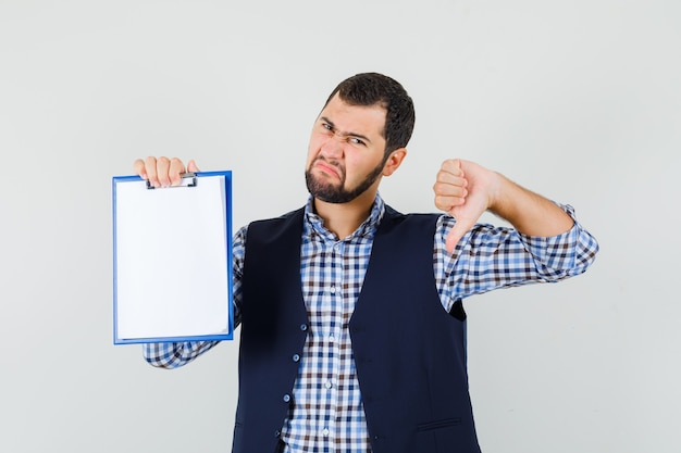 Giovane che tiene appunti con il pollice verso il basso in camicia, gilet e guardando malcontento, vista frontale.