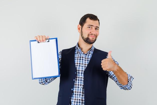 Молодой человек держит буфер обмена с большим пальцем руки вверх в рубашке, жилете и выглядит весело, вид спереди.