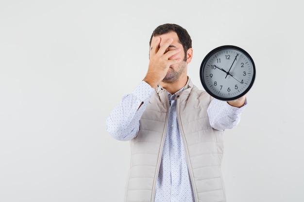 Молодой человек держит часы в одном и закрывает часть лица рукой в бежевой куртке и кепке и выглядит взволнованным. передний план.