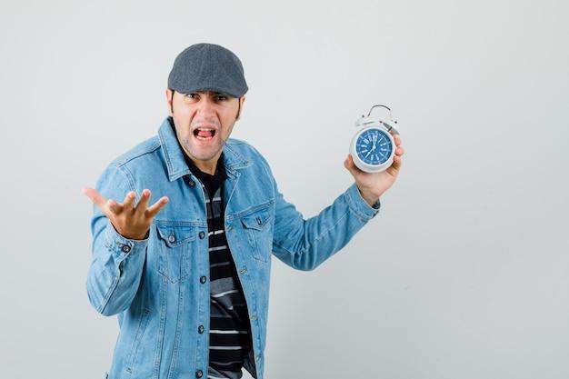 Giovane che tiene l'orologio mentre alza le mani in modo aggressivo in giacca, berretto e sembra arrabbiato