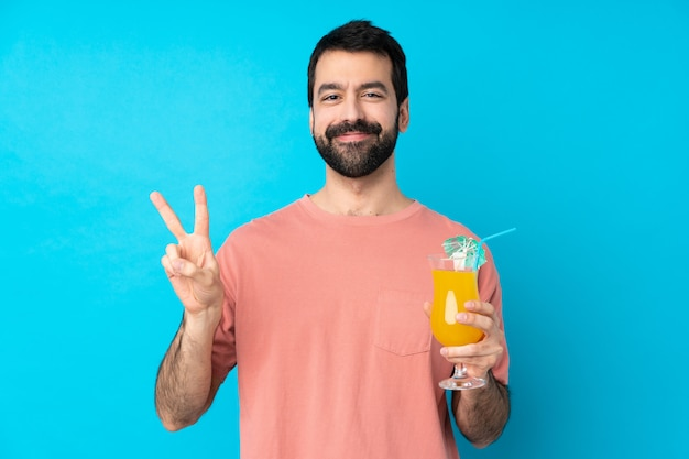 Young man over holding a cocktail over isolated blue wall showing victory sign with both hands