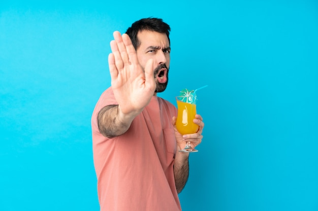 Young man over holding a cocktail making stop gesture and disappointed
