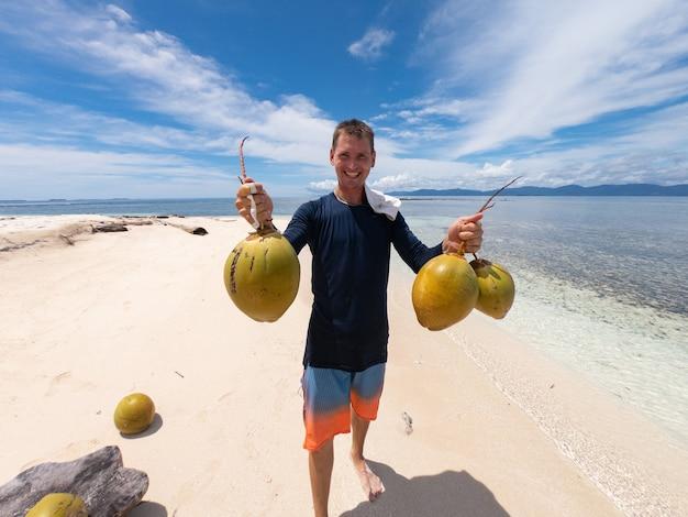 Молодой человек держит кокосы на песчаном пляже с водой и небом на фоне приключений и путешествий ...