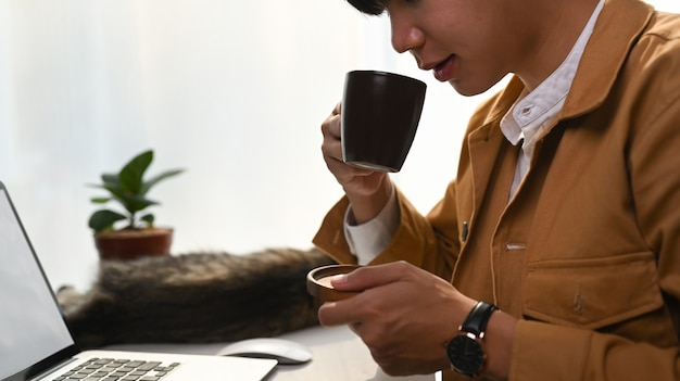 Young man holding coffee cup on home workplace.