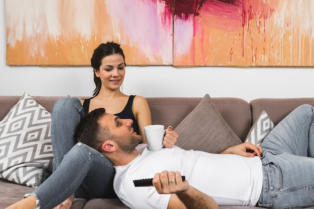 Young man holding coffee cup and remote control lying on woman's lap