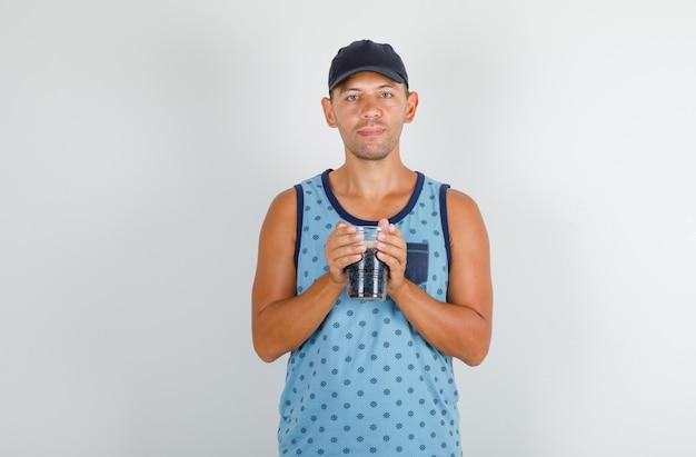 Молодой человек держит холодную колу в синей майке с кепкой