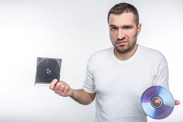 Young man holding a compact disk in one hand and a box from it in another hand and staring at camera. time goes so fast that now he doesn't know what to do with this disk. isolated on white wall