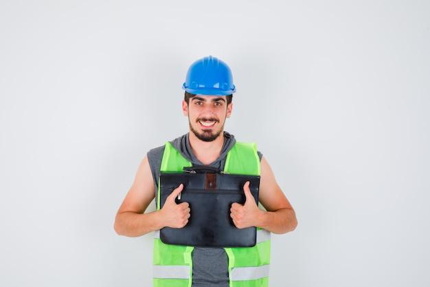 건설 도구 케이스를 들고 건설 유니폼에 엄지 손가락을 보여주는 젊은 남자와 행복을 찾고