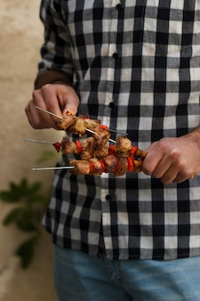Young man holding cooked barbecue