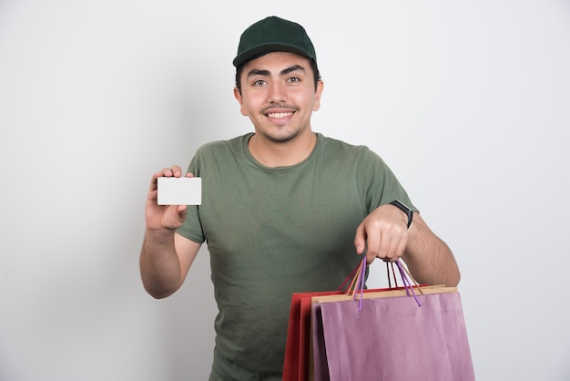 Young man holding credit card and shopping bags on white background.