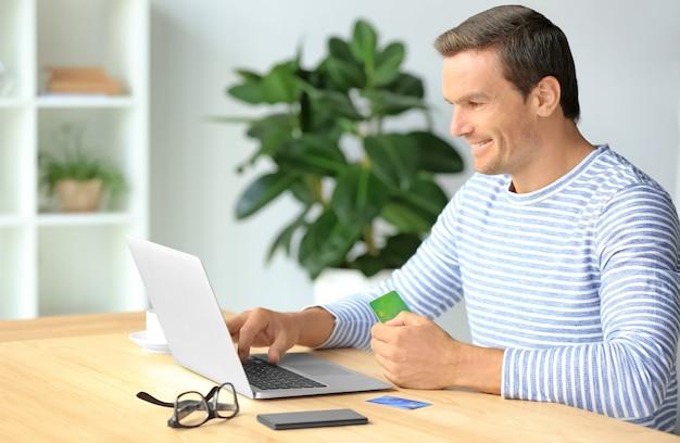 Молодой человек, держащий кредитную карту при использовании ноутбука дома