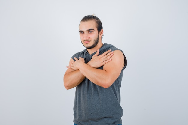 ノースリーブのパーカーで胸に交差した腕を保持し、インテリジェントに見える若い男。正面図。