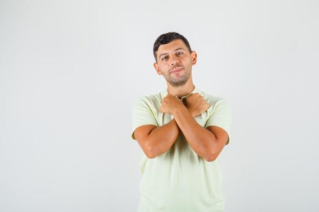 Молодой человек держит скрещенные кулаки возле шеи в футболке и выглядит счастливым