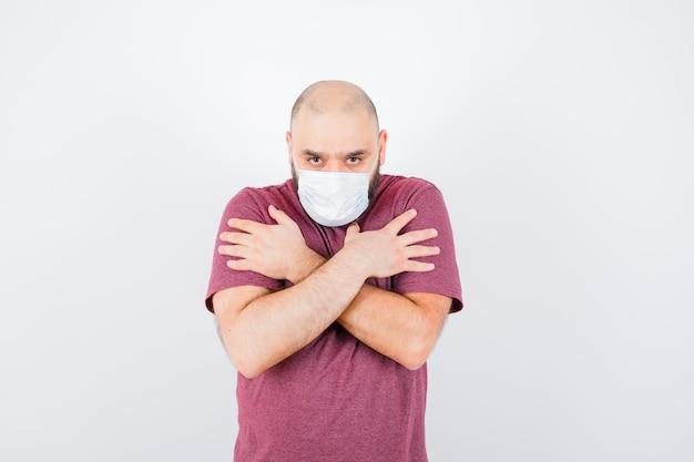 분홍색 티셔츠, 마스크를 쓰고 진지한 표정으로 어깨에 손을 얹고 있는 젊은 남자. 전면보기.