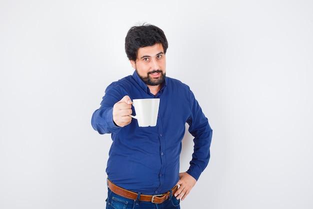 Молодой человек держит чашку и держит руку на талии в голубой рубашке и джинсах и выглядит оптимистично. передний план.