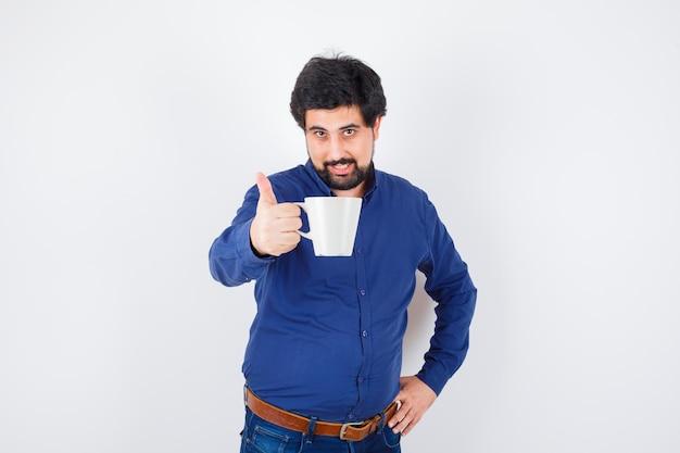 젊은 남자 컵을 들고 파란색 셔츠와 청바지에 허리에 손을 잡고 낙관적 찾고. 전면보기.