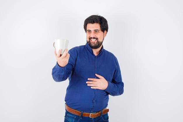 Молодой человек держит чашку и смотрит на нее в голубой рубашке и джинсах и смотрит оптимистично, вид спереди.