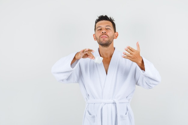 Young man holding cup of coffee in white bathrobe and looking spirited , front view.