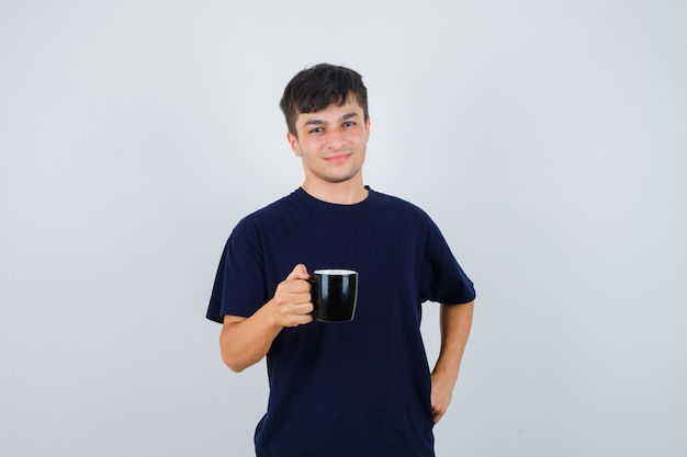 Giovane che tiene tazza di bevanda in maglietta nera e guardando orgoglioso, vista frontale.