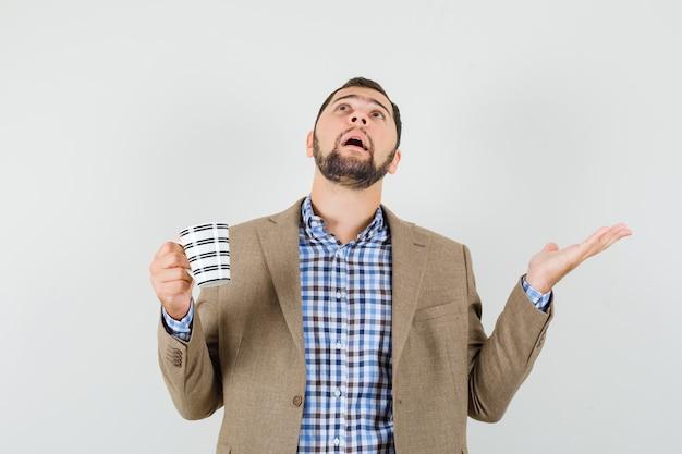 Giovane che tiene tazza di bevanda, alzando lo sguardo in camicia, giacca e guardando confuso, vista frontale.