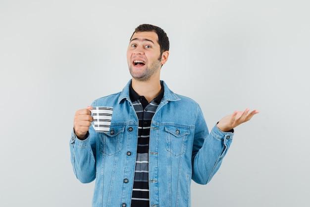 Giovane che tiene una tazza di bevanda, allargando il palmo da parte in maglietta, giacca e guardando gioviale.