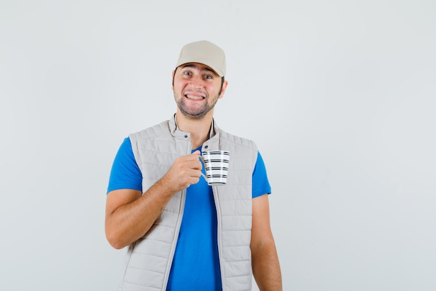 Young man holding cup of drink in t-shirt, jacket and looking merry. front view.