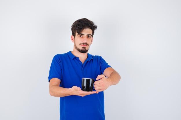 파란색 티셔츠에 컵을 들고 심각한 찾고 젊은 남자