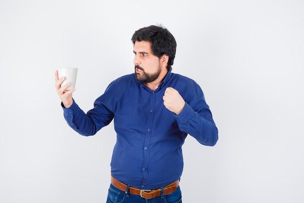 Giovane che tiene tazza e lo guarda, stringendo il pugno in camicia blu e jeans e sembra furioso. vista frontale.