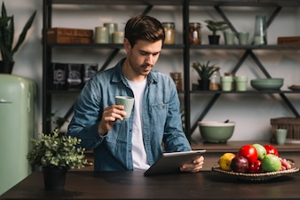 Young man holding cup of coffee looking at digital tablet