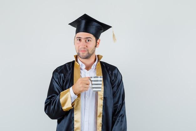대학원 유니폼에 음료 한잔 들고 우아한 찾고 젊은 남자. 전면보기.
