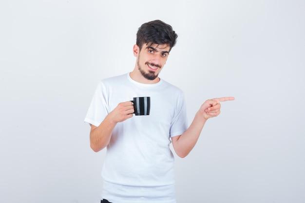 飲み物を持って、白いtシャツを脇に向け、自信を持って見える若い男