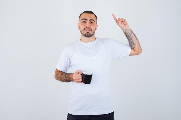 お茶を持って、白いtシャツと黒いズボンでユーレカジェスチャーで人差し指を上げて幸せそうに見える若い男