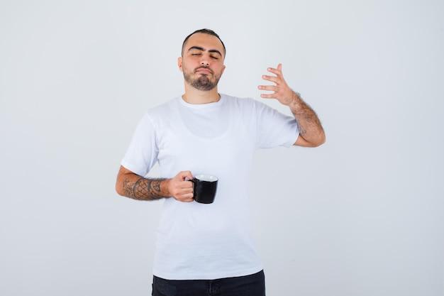 白いtシャツと黒いズボンで目を閉じて落ち着いて見える間、お茶を持って手を伸ばして想像上の何かを持っている若い男